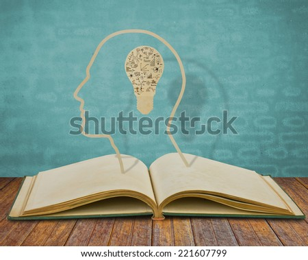 Paper cut of book and  light bulb inside a head with drawing graph - stock photo