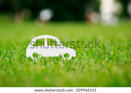 Paper cut of car on green grass