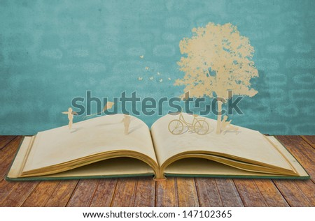 Paper cut of children play on old book - stock photo