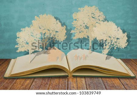 Paper cut of family symbol on old book  ( House,Tree,Mom,Dad,Child  ) - stock photo