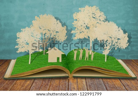 Paper cut of family symbol on old grass book ( House,Tree,Mom,Dad, Child ) - stock photo