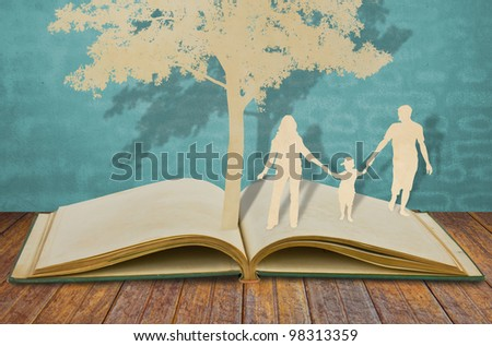 Paper cut of family symbol under tree on old book - stock photo