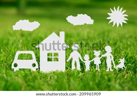 Paper cut of family with house and car on green grass - stock photo