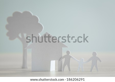 Paper cut of family with house and tree - stock photo