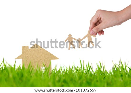 Paper cut of house on fresh spring green grass
