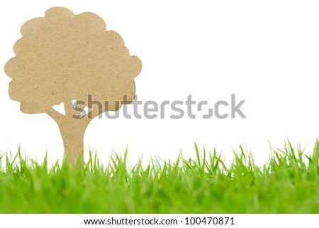 Paper cut of  tree on fresh spring green grass - stock photo