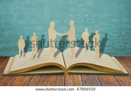 Paper cut of two business man shake hand on old book - stock photo