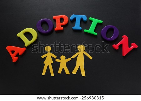 Paper cutout family of three with Adoption letters                                - stock photo