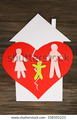 Paper cutout silhouette of a family split apart on a paper heart, divorce concept - stock photo