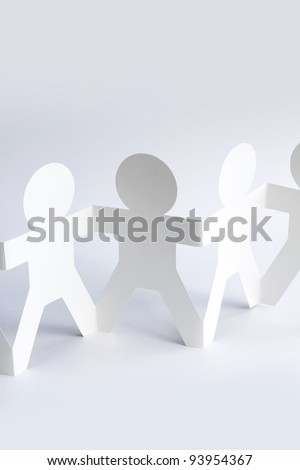 Paper doll people holding hands. Copy space - stock photo