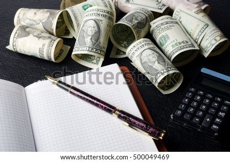 Paper dollars, notebook, fountain pen, calculator