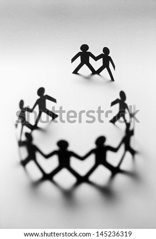 Paper dolls in circle with two bystanders - stock photo