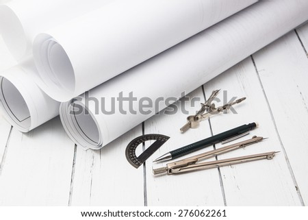 Paper drawing with compasses and pencils on a white wooden background - stock photo