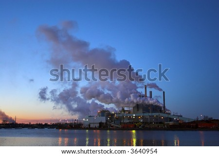 Paper factory pipers with the clouds of smoke in the nighttime sky reflected in the river.