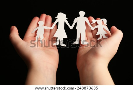 Paper family in child hands on black background