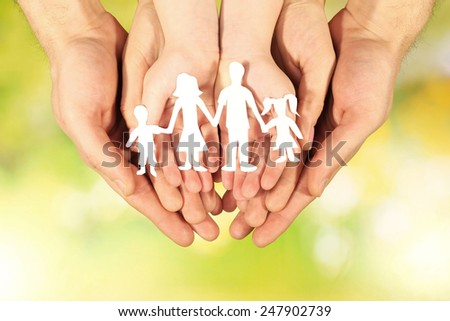 Paper family in hands on bright background - stock photo