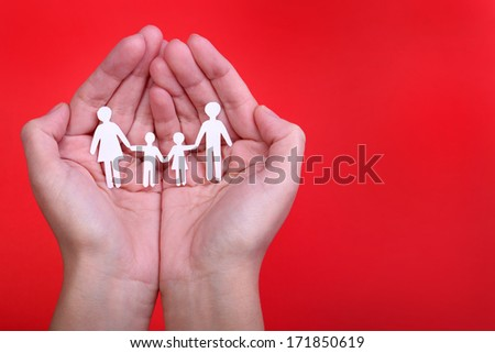 Paper Family in Hands over red background. Family and Kids Concept