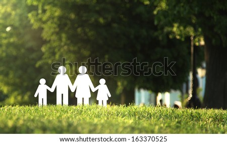 paper family on green grass - stock photo