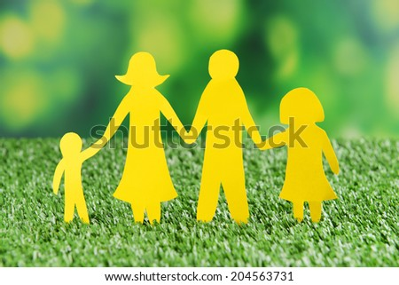 Paper family on green grass, close up - stock photo