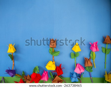 paper flowers on blue background. - stock photo