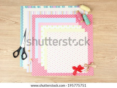 Paper for scrapbooking and tools, on wooden table - stock photo