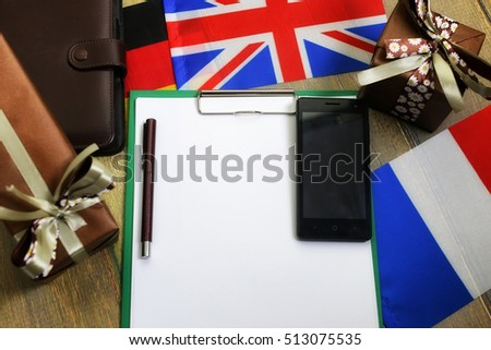 paper form a texture on a wooden table with gift boxes packed mobile phone and flags