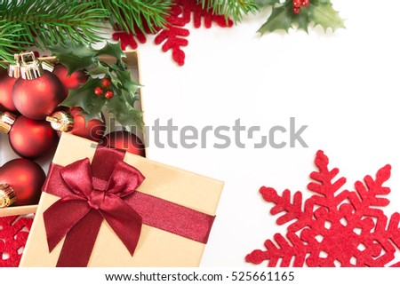Paper gift box with a red bow and Christmas balls, on white background.