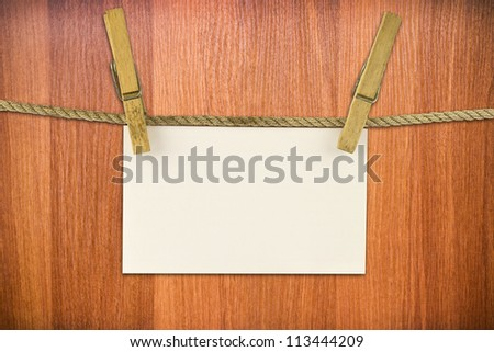 paper hang on clothesline with clipping path on wood background - stock photo