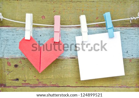 Paper heart and card hanging on the clothesline. On old wood background.Valentines day theme . - stock photo