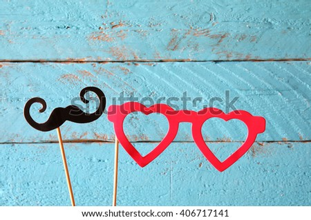 paper heart shape fake glasses and mustaches in sticks in front of wooden background. vintage filtered image