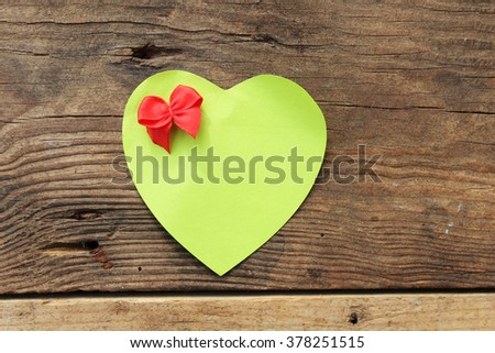Paper heart with bow on wooden background and copy space - stock photo