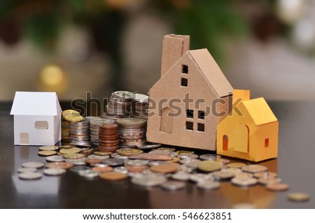 Paper house and stacks of coins standing. House loan concept