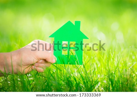 Paper house in children`s hand against green spring background. Real estate concept - stock photo