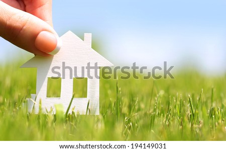 Paper house in green grass over blue sky. Concept of construction or mortgage. Eco - stock photo