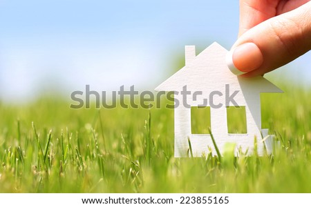 Paper house in green grass over blue sky. Mortgage concept  - stock photo
