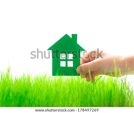 Paper house in hand over spring green grass. Real estate concept