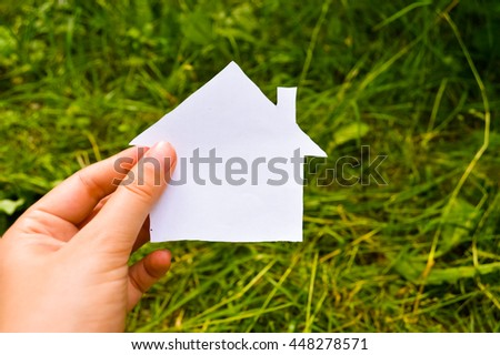 Paper house on a background of green grass.