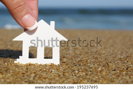 Paper house on the beach. Concept of mortgage. Macro - stock photo