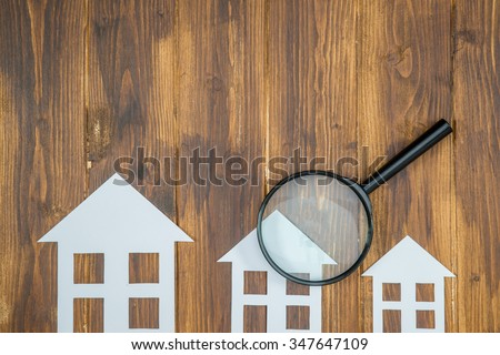 paper house with Magnifying Glass, House hunting on wooden background - stock photo