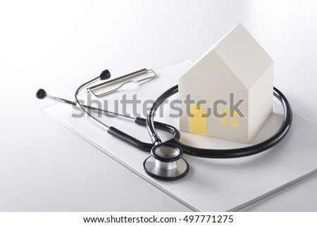 Paper house with stethoscope on white background