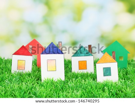 paper houses on green background, close up - stock photo