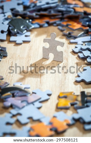 Paper jigsaw puzzle surrounded by pieces  on a table . Shallow depth of field - stock photo