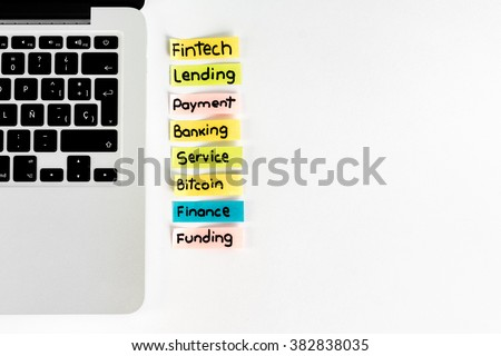 Paper labels with financial words like fintech, lending, payment, banking services, with a notebook computer over desk.