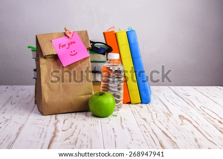paper  lunch bag  with apple,water and books  on desk with post-it note, - stock photo