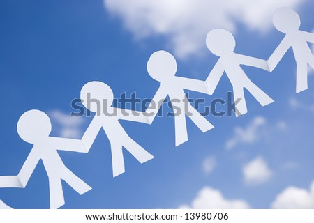 Paper man chain on blue sky with white clouds. Symbol of unity, brotherhood and teamwork. - stock photo