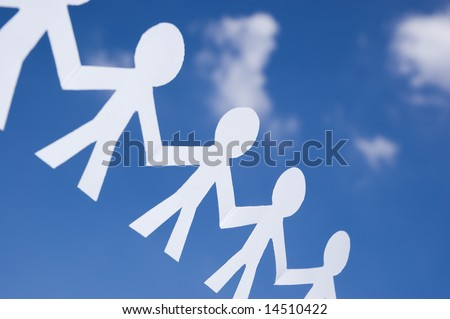 Paper man chain on blue sky with white clouds. Symbol of unity, brotherhood and teamwork - stock photo