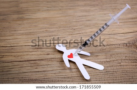 Paper man with heart and syringe on wooden background. Drug Addiction Concept.  - stock photo