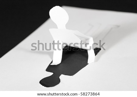Paper man with the upper part of the body cut out of paper (getting ready to rise) - stock photo