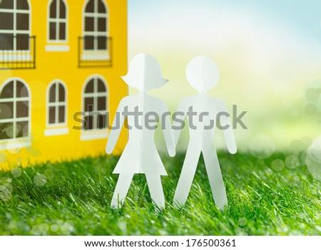 paper men family beside new house - stock photo