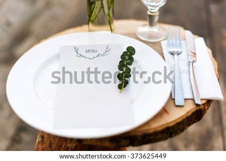Paper menu on decorated table ready for dinner. Beautifully decorated table set with flowers, plates and serviettes for outdoor wedding ceremony or another event in the restaurant. Selective focus - stock photo